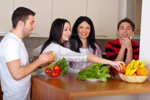 happy-group-of-friends-preparing-food-with-fresh-vegetables-and-having-conversation-in-kitchen